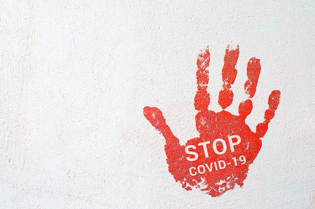 Uma impressão da mão com a inscrição stop covid19 em uma parede de concreto leve