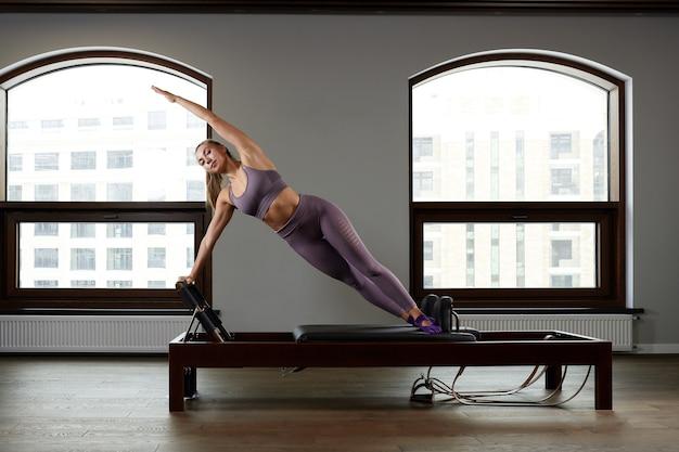 Uma instrutora de ioga treina em um cadillac reformado em um grande salão contra uma janela, equipamento moderno para treinamento em academias, correção do sistema músculo-esquelético.