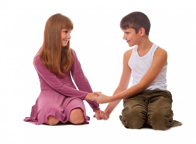 Uma irmã e um irmão jogam juntos enquanto se sentam ao lado um do outro no chão.