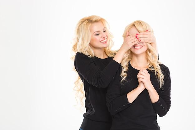 Uma irmã gêmea loira alegre cobriu os olhos de outra
