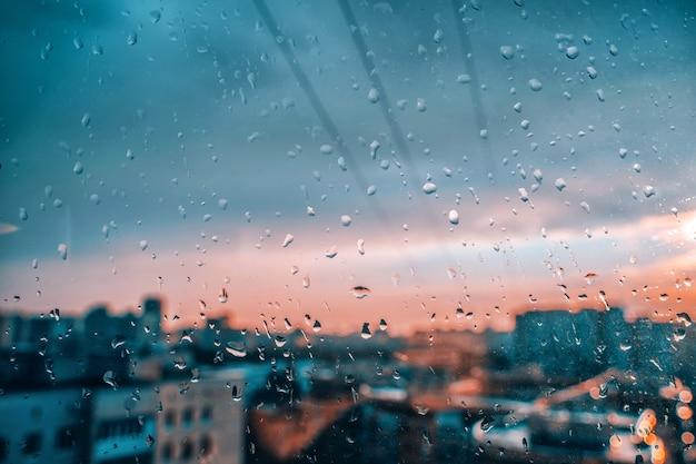 Uma janela com gotas de chuva de uma cidade e nuvens ao fundo