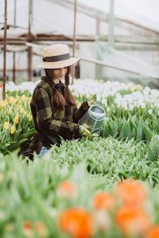 Uma jardineira de chapéu e luvas rega um canteiro de tulipas usando um regador