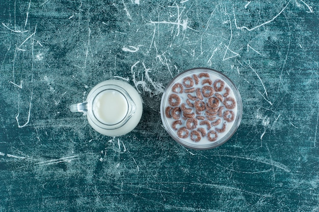 Uma jarra de leite ao lado de um copo de anel de milho com leite, no fundo azul. foto de alta qualidade