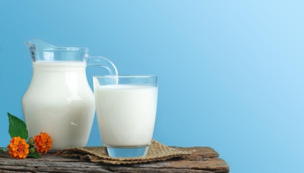 Uma jarra de leite e um copo de leite em uma mesa de madeira sobre um fundo azul.