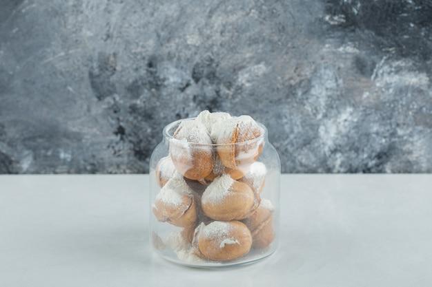 Uma jarra de vidro cheia de biscoitos doces em forma de noz.