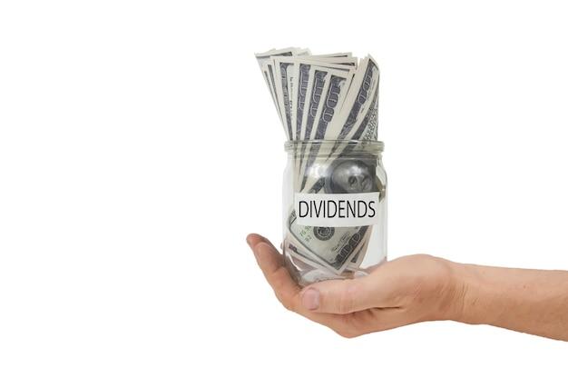 Uma jarra de vidro com a inscrição de dividendos no rótulo, cheia de notas de cem dólares em uma mão estendida sobre um fundo branco isolado