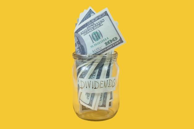 Uma jarra de vidro com as palavras dividendos no rótulo, cheia de notas de cem dólares em um fundo amarelo