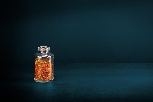 Uma jarra de vidro com comprimidos de laranja em fundo escuro