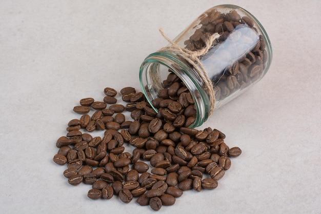 Uma jarra de vidro com grãos de café na superfície branca