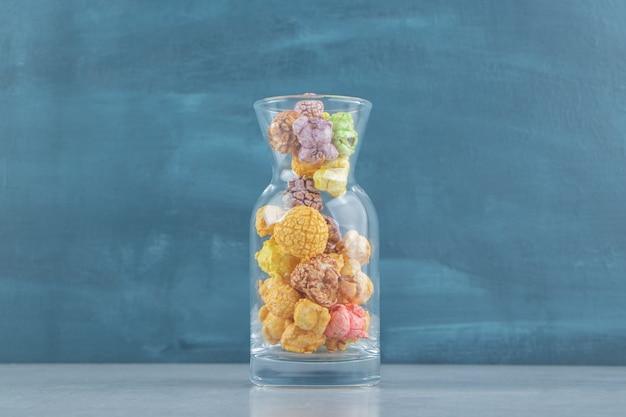 Uma jarra de vidro com pipoca doce multicolorida.