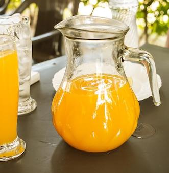 Uma jarra de vidro com suco de laranja em uma pequena mesa do lado de fora à luz do dia