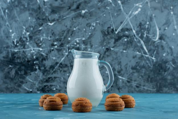 Uma jarra de vidro de leite fresco com biscoitos redondos doces em uma superfície azul