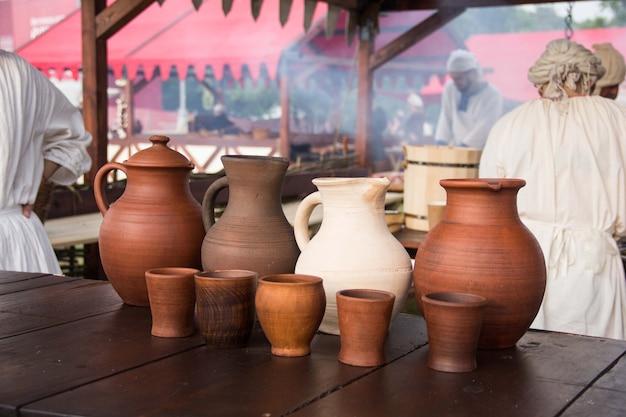 Uma jarra de vinho e um conjunto de xícaras de barro na mesa de madeira.