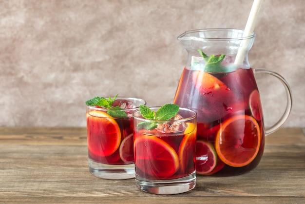 Uma jarra e dois copos com frutas espanholas sangria