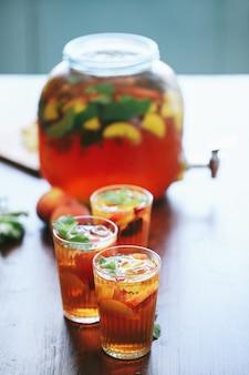 Uma jarra grande e três xícaras de suco de pêssego