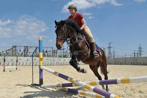 Uma jóquei cavalgando um cavalo pula uma barreira