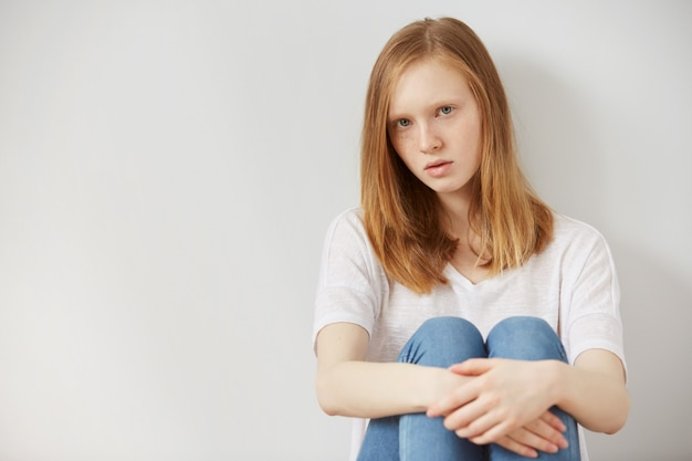 Uma jovem adolescente bonita sentada no chão em casa desesperada, triste sozinha