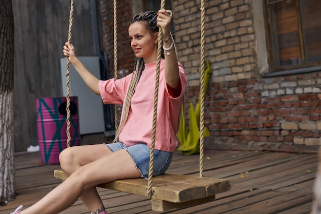 Uma jovem adolescente com tranças e uma camiseta rosa balançando em um balanço de madeira contra o fundo ...