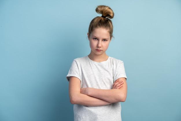 Uma jovem adolescente cruza os braços sobre o peito e olha para a frente em uma parede azul