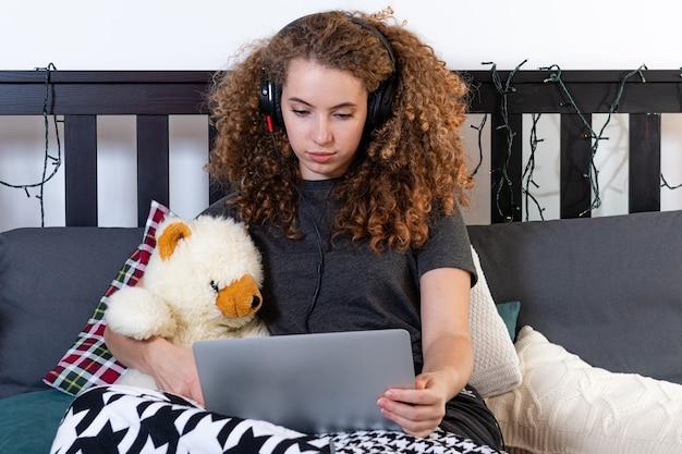 Uma jovem adolescente encaracolada com um ursinho de pelúcia está sentada na cama e assiste a um filme em seu laptop