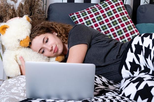 Uma jovem adolescente encaracolada deitada na cama pega um ursinho de pelúcia e olha para a tela do laptop