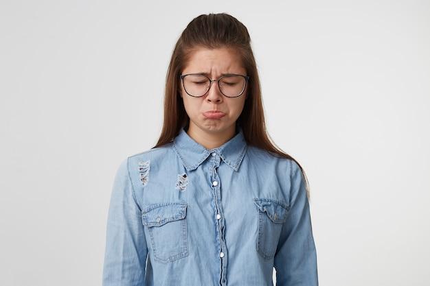 Uma jovem adolescente muito triste fechou os olhos, chorou, virou o lábio, chateada ofendida ofendida, vestida com camisa jeans, isolada em uma parede branca.