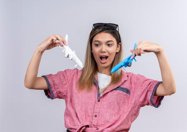 Uma jovem adorável e animada vestindo uma camisa vermelha com óculos de sol, olhando surpreendentemente para aviões de brinquedo brancos e azuis enquanto os pilotava