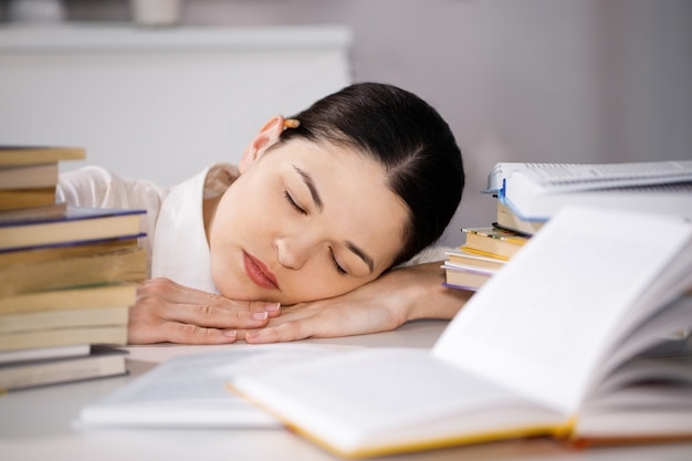 Uma jovem adormecida na frente de uma pilha de papéis e um computador segurando sua cabeça