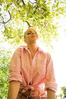 Uma jovem adulta colhendo maçãs orgânicas em um dia ensolarado em seu jardim.