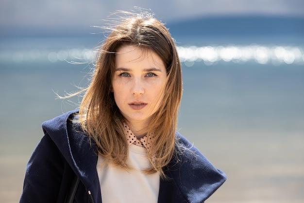 Uma jovem adulta menina bonita fica na praia no contexto de uma nuvem se aproximando com chuva. a mulher está usando um vestido irregular, um suéter branco e um casaco azul marinho.