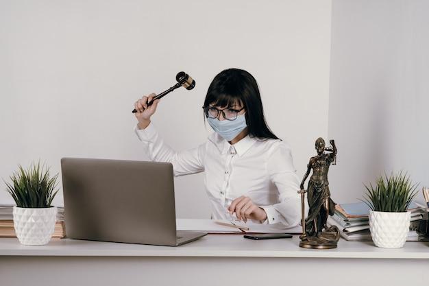 Uma jovem advogada ou juíza trabalha remotamente no escritório com uma máscara protetora durante uma epidemia.