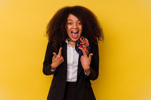 Uma jovem aeromoça afro-americana isolada em um fundo amarelo surpreendeu apontando com o dedo, sorrindo amplamente.