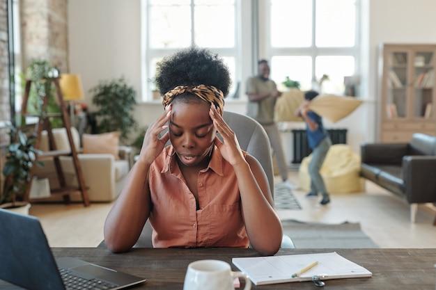 Uma jovem africana cansada tocando a cabeça enquanto está sentada à mesa em frente ao laptop durante a rede contra o marido brincando com o filho pequeno