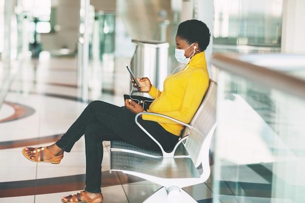 Uma jovem africana com uma máscara protetora está sentada em uma cadeira na sala de espera, ouvindo música com fones de ouvido e esperando o trem do metrô. distância social, pandemia.