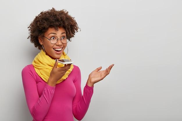 Uma jovem africana feliz usa reconhecimento de voz em smartphone, levanta a palma da mão e sorri amplamente isolado sobre um fundo branco