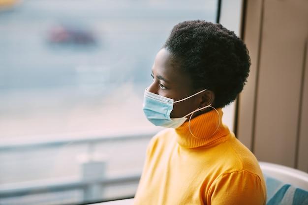 Uma jovem africana usando uma máscara protetora viaja em um ônibus e olha pela janela. coronavírus, distância social. vista lateral.
