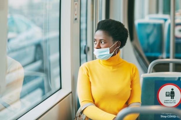 Uma jovem africana usando uma máscara protetora viaja em um ônibus e olha pela janela. coronavírus, distância social.