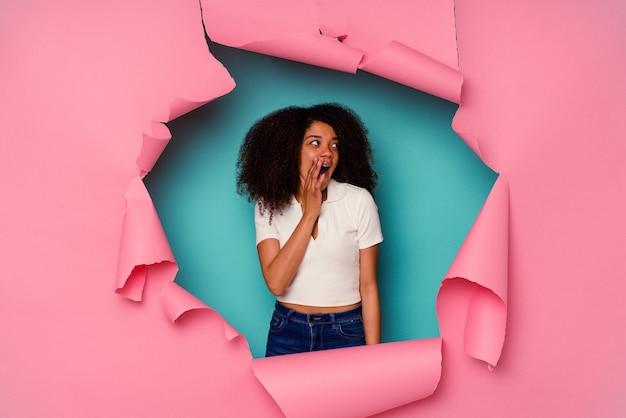 Uma jovem afro-americana em um papel rasgado, isolado em um fundo azul, está contando uma notícia secreta de travagem e olhando para o lado