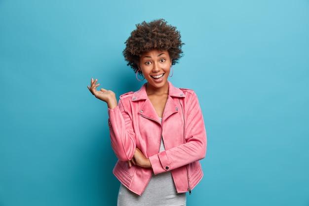 Uma jovem afro-americana feliz e terna com uma jaqueta rosa levanta a mão, mostra dentes brancos perfeitos, alegra-se com boas notícias, tem cabelo encaracolado, poses