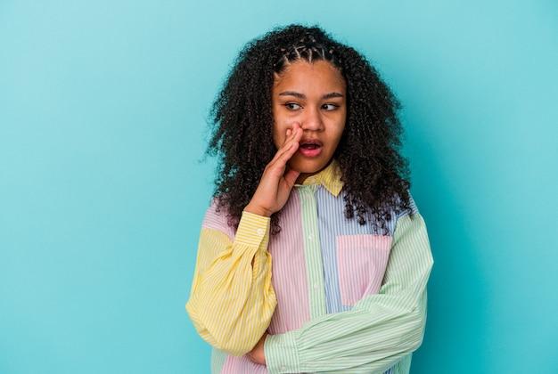 Uma jovem afro-americana isolada em um fundo azul está contando uma notícia secreta de travagem e olhando para o lado