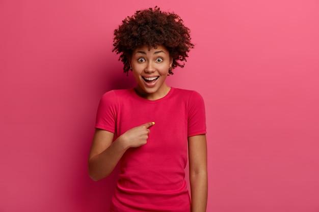 Uma jovem afro-americana positiva aponta para si mesma com empolgação, fica feliz com uma reação inesperada, pergunta se você está brincando comigo, ri positivamente, usa uma camiseta vermelha, posa contra uma parede rosa