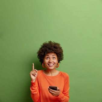 Uma jovem afro-americana positiva segura um smartphone moderno indica para cima com o dedo indicador demonstra o espaço da cópia para seu anúncio isolado sobre a parede verde