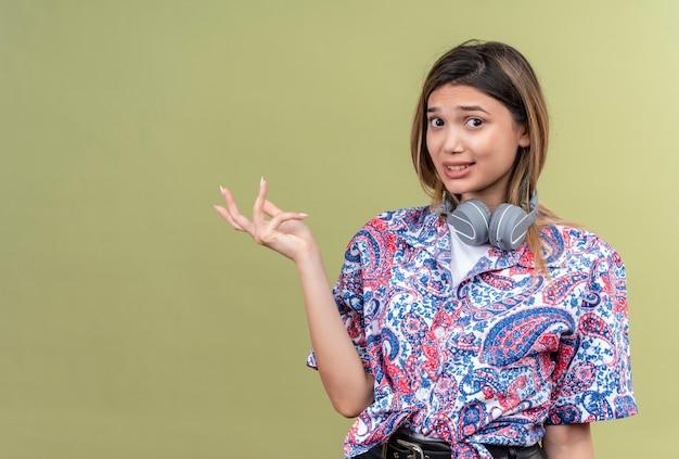 Uma jovem agressiva com uma camisa estampada de paisley e fones de ouvido levantando a mão