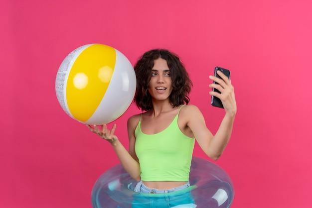Uma jovem alegre com cabelo curto em um top verde, segurando uma bola inflável, tirando uma selfie com o celular em um fundo rosa