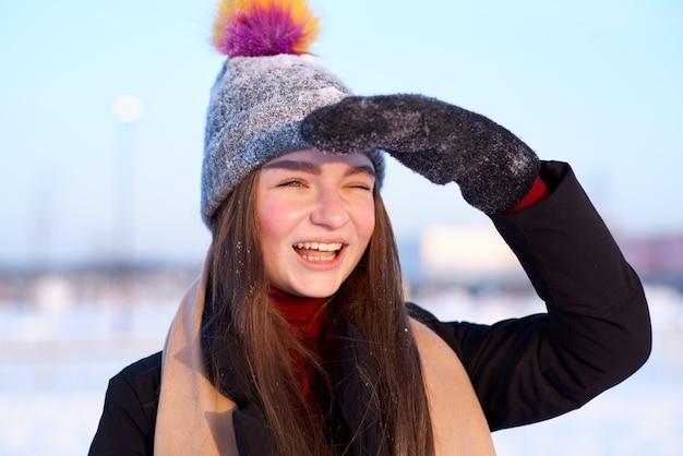 Uma jovem alegre, com um chapéu de inverno e luvas com uma expressão divertida e alegre fecha os olhos do sol com a mão