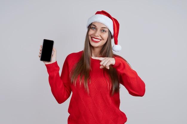 Uma jovem alegre com um chapéu de papai noel e um telefone nas mãos aponta o dedo para a tela. conceito de compras online, saudações online, descontos de natal.