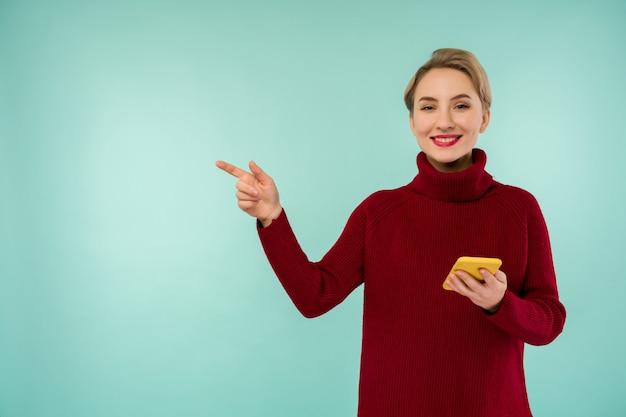 Uma jovem alegre com um suéter vermelho e um smartphone em um fundo azul