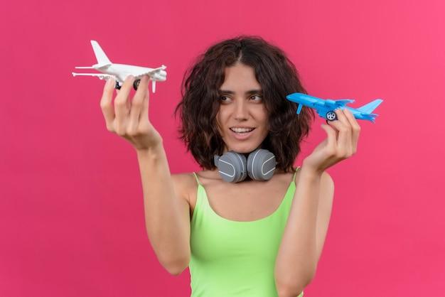 Uma jovem alegre e atraente mulher com cabelo curto e top verde recortado em fones de ouvido segurando aviões de brinquedo azuis e brancos