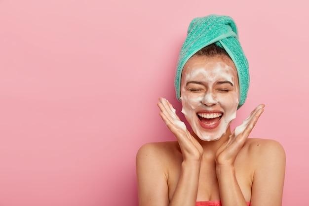 Uma jovem alegre e feliz espalha as palmas das mãos no rosto, lava o rosto com sabonete, se diverte no banheiro, mima a pele, usa uma toalha enrolada na cabeça, expressa emoções positivas