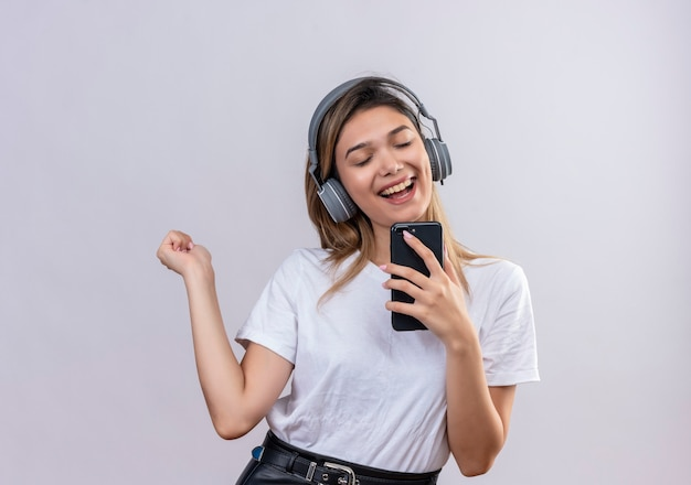 Uma jovem alegre em uma camiseta branca usando fones de ouvido cantando enquanto ouve música em seu telefone em uma parede branca